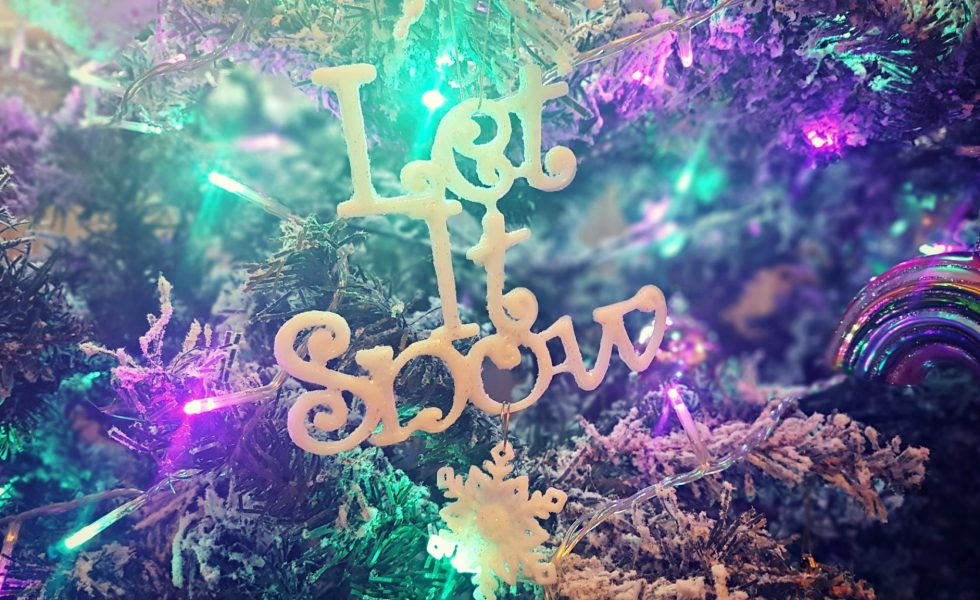let it snow decroation on a christmas tree with green and purple lights on