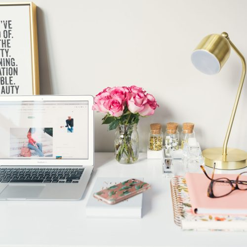 a desk set up with lamp, notebooks, frames, plants and accessories