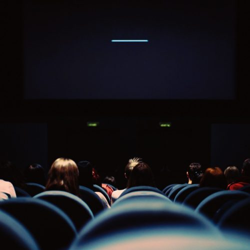 a cinema screening room in the dark showing the backs of chairs