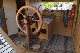 Note the pulleys. This wheel is mounted on the end of the tiller, and turning the wheel operates ropes that pull it left or right
