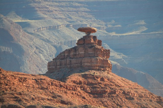Mexican Hat Rock from a little distance with the canyon wall of the San Juan River in the background.