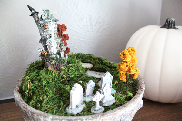 Halloween terrarium with a witch house and a graveyard