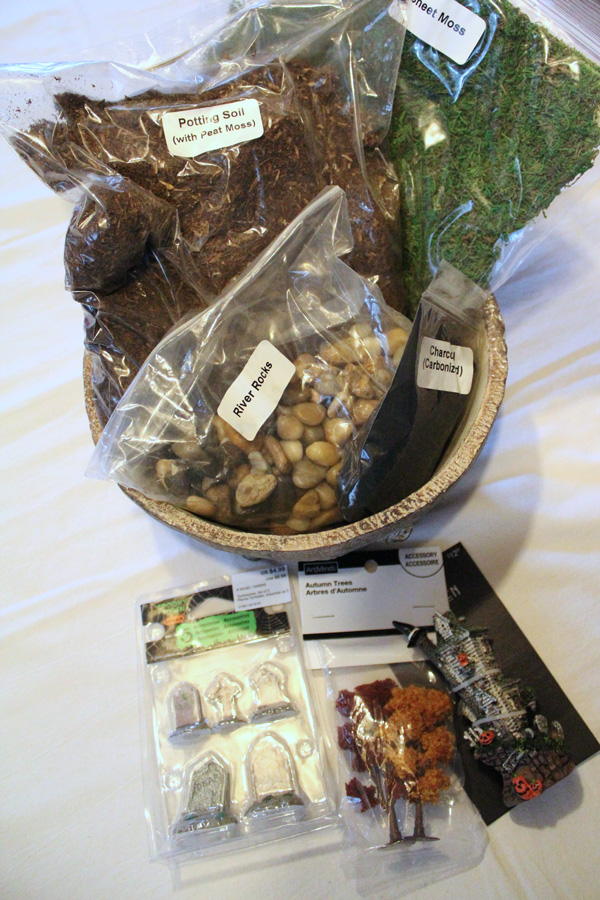 Halloween terrarium supplies: container, rocks, charcoal, potting soil, moss, and miniatures