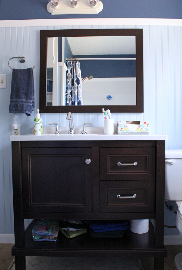 bathroom remodel: sink vanity and mirror with fixtures and blue walls