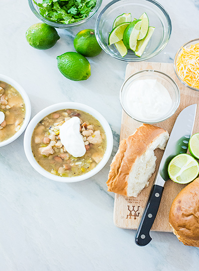 white chicken chili ready to eat in a bowl with garnishes of sour cream, cheese, lime and cilantro