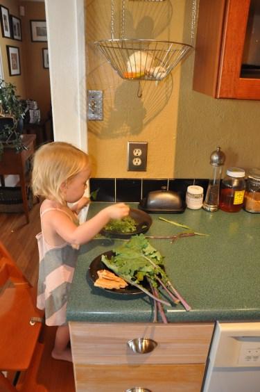 Trimming/tearing kale (and nibbling on pancakes)