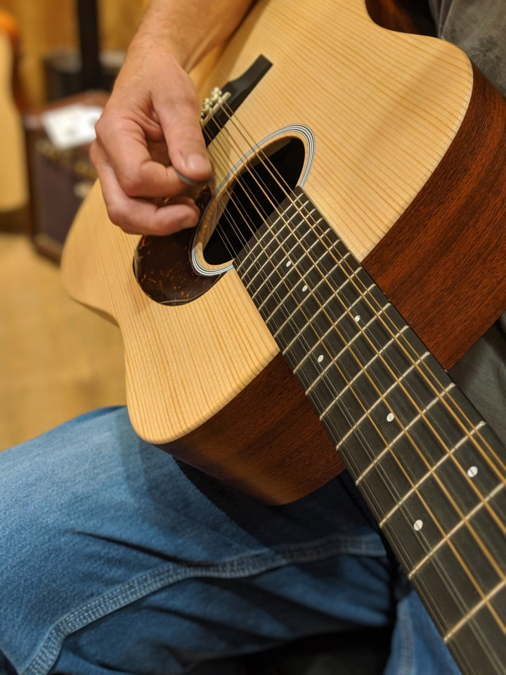 This is a photo of someone Playing a 12 string acoustic guitar.