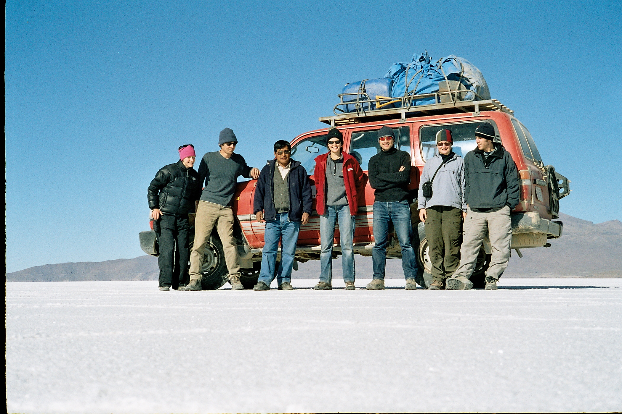 The author with her partner, four new friends and their driver standing on the vast white expanse of the Bolivian salt lake, the Salar de Uyuni, with a bright blue sky above.