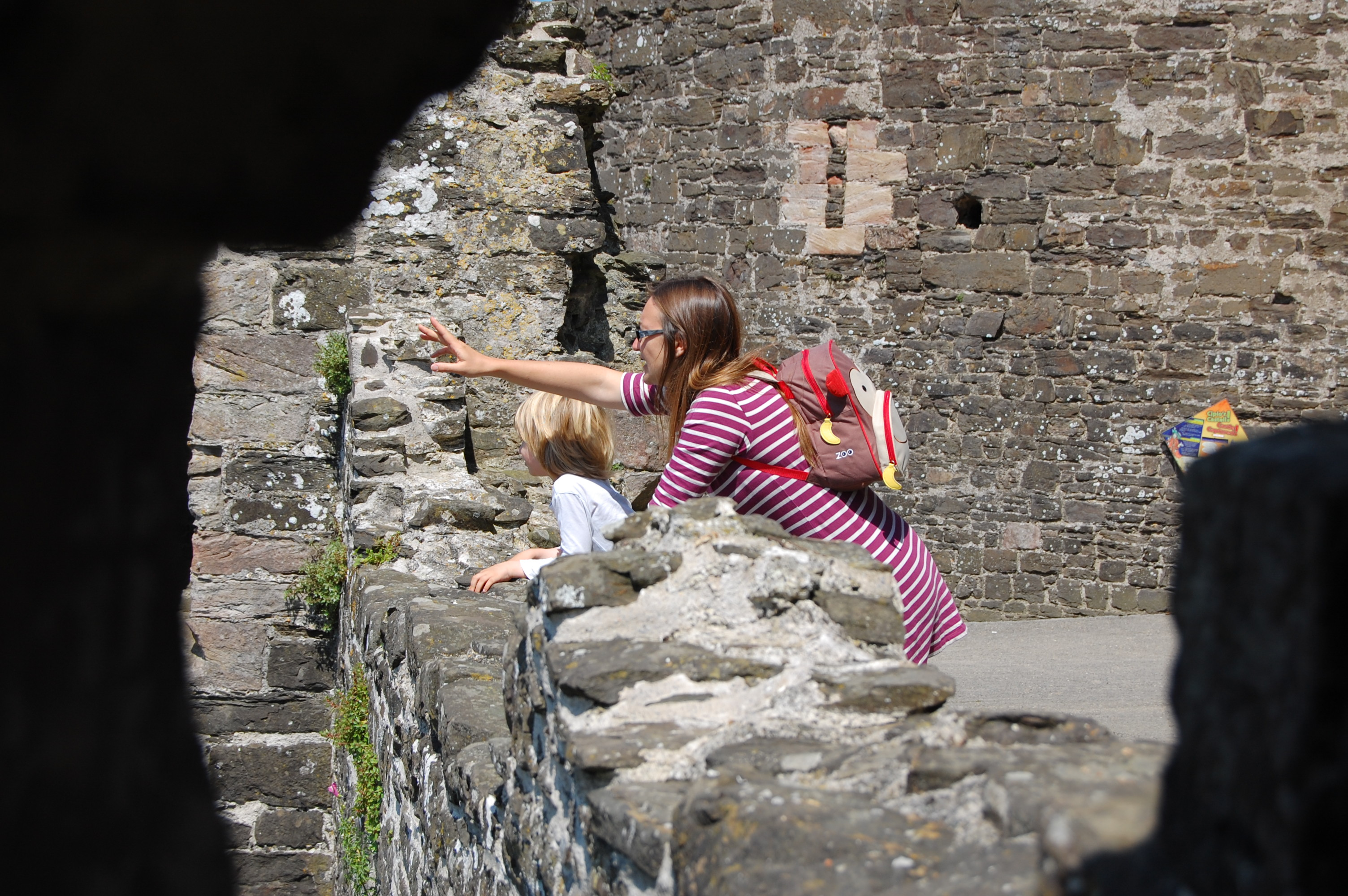 The author and her son pointing from the edge of a wall at Conwy castle in North Wales.