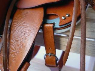Tan saddle with embossed flame detail - closeup of cinch holder