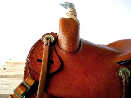 Tan saddle with embossed flame detail - closeup of latigo holder