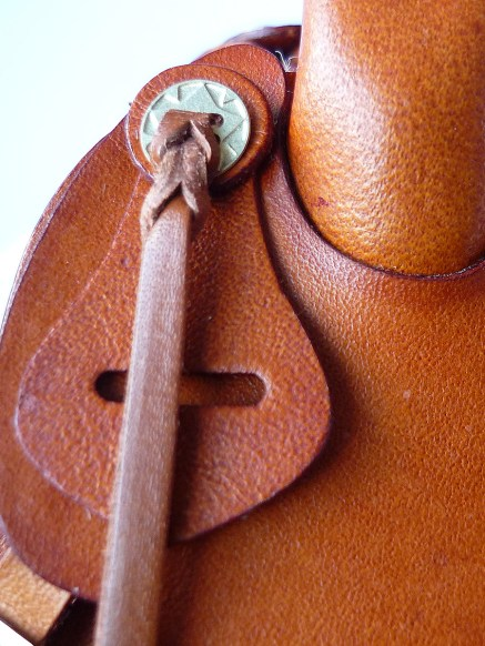 Tan saddle with embossed flame detail - closeup of latigo holder