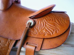 Tan saddle with embossed flame detail - closeup of rear concho