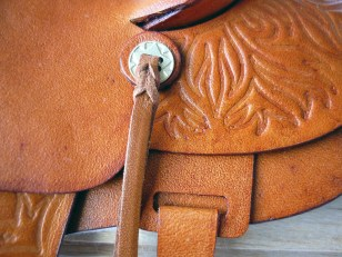 Tan saddle with embossed flame detail - closeup of concho