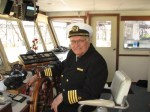 Captain and Reverend Bruce Hudec at the wheel of the Goodtime III