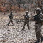 A group of airsoft players walking through a wood