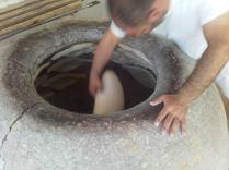 Das Khachapuri wird mit einer Art Kelle an die Wand des Lehmofens geklatscht. Nette Angelegenheit bei 35°C über der heißen Öffnung.