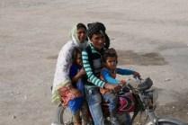 Vier Menschen auf einem Moped: Supernette Familie beim Mittagsstopp auf einer Raststätte.