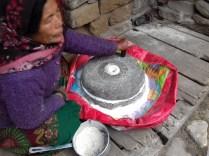 Sherpafrau mit Getreidemühle.