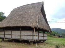 Dorfgemeinschaftshaus auf dem Weg zurück nach Laos. Innen klettern Kinder affenartig im hohen Dachstuhl rum.