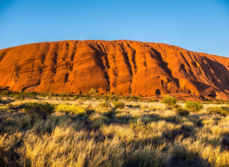 Les formes d'Uluru se revèlent avec le soleil sur le Base walk