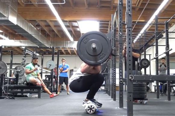 Man-squats-315-lbs-while-on-a-hoverboard-segway