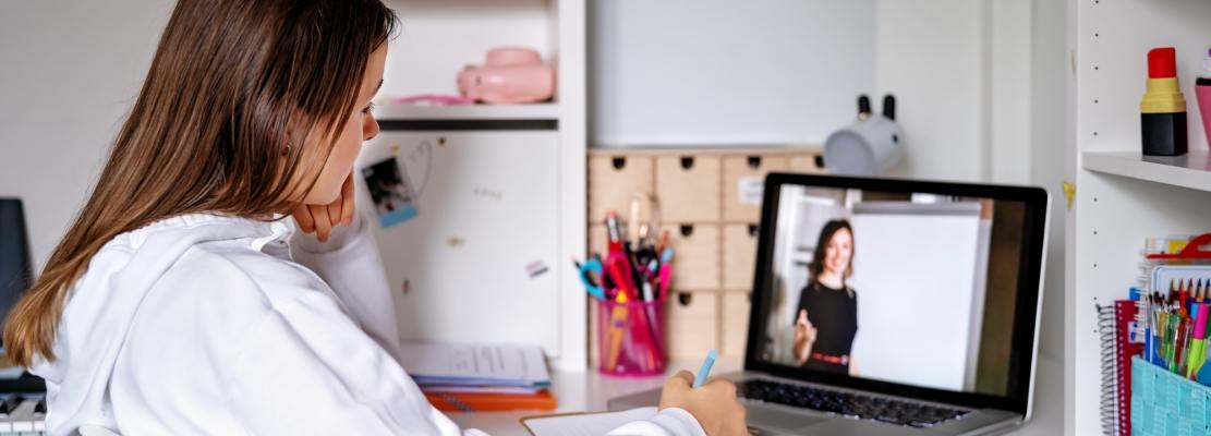 Teenager girl studying online at home looking at teacher giving lesson at laptop screen at