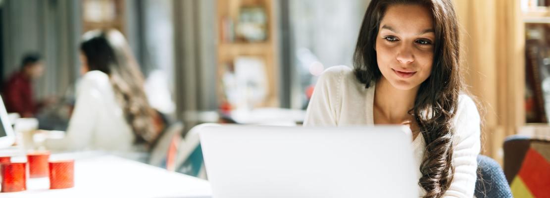 Brunette using laptop in cafe
