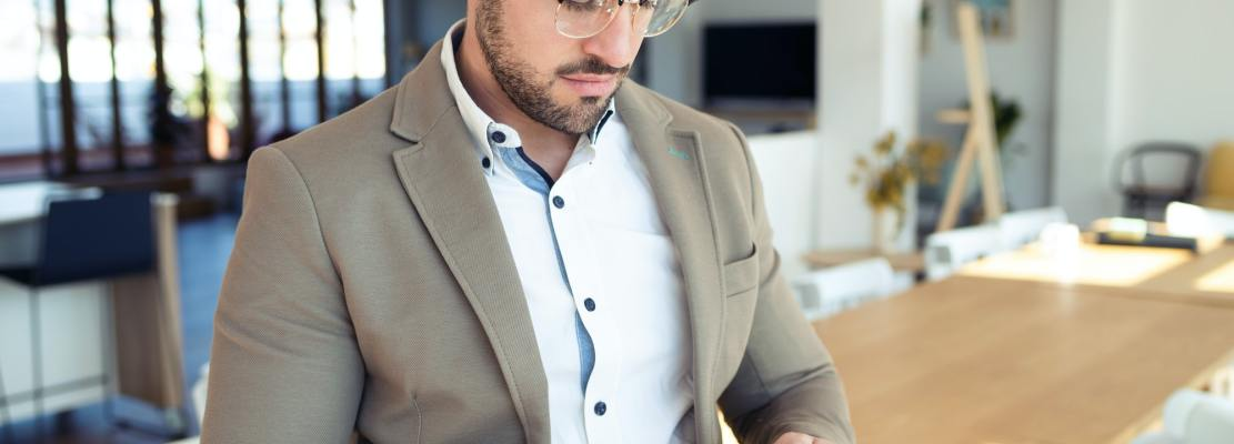 Handsome young business man using his smartphone while sitting on table in the office.