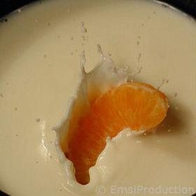 Slice of orange falling into a glass of milk