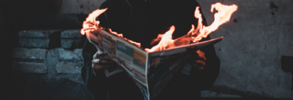 fake reviews are the fake news of the local SEO world, illustrated by man reading burning newspaper