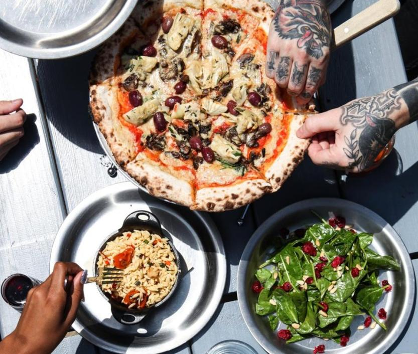 Hands grabbing pizza, salad and pasta salad.