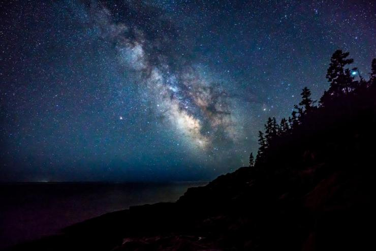 Milky Way and stars shine off the coast of Acadia National Park