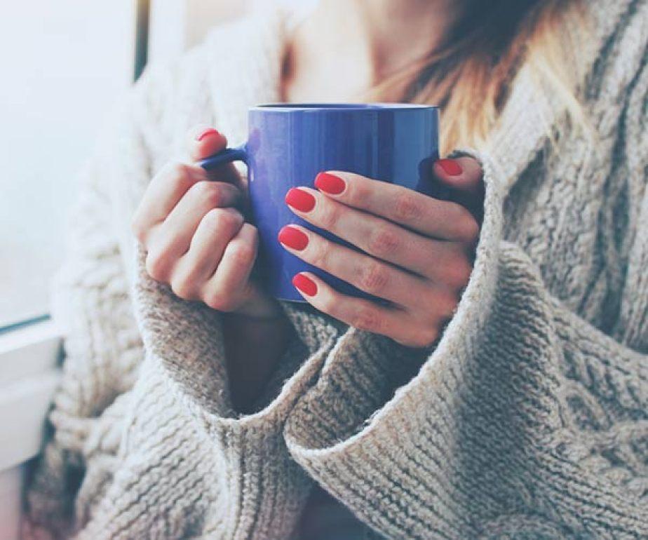 woman holding blue coffee mug
