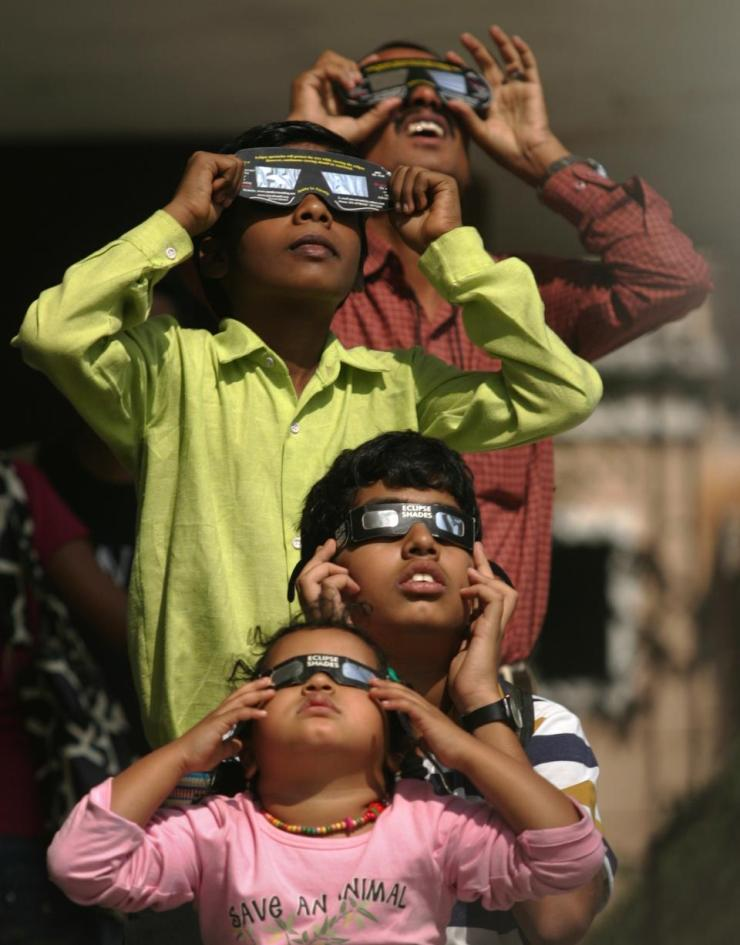 People use solar viewers to view an annular solar eclipse at the Nehru planetarium in Mumbai in December 2010. (Photo by Satish Bate/Hindustan Times via Getty Images)