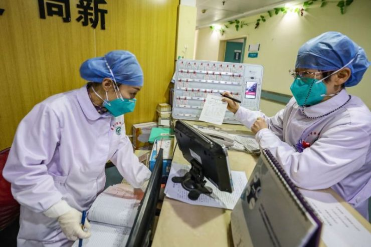 This photo taken on January 30, 2020 shows medical staff members wearing facemasks talking at a hospital in Wuhan in China's central Hubei province, during the virus outbreak in the city. - The World Health Organization declared a global emergency over the new coronavirus, as China reported January 31 the death toll had climbed to 213 with nearly 10,000 infections.