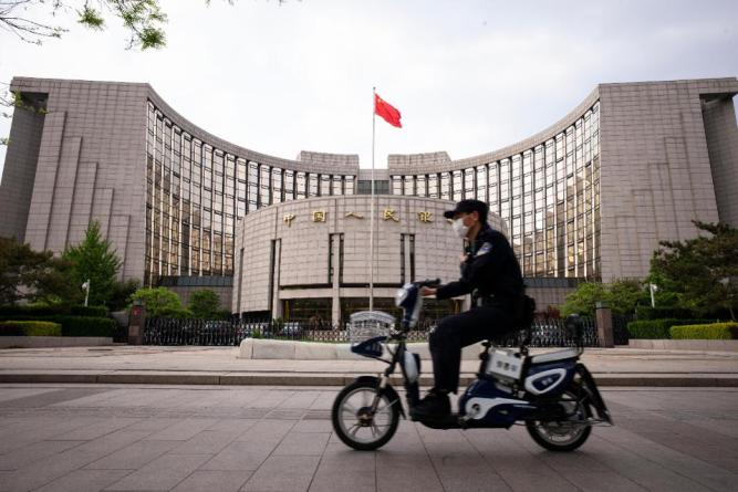 Chinese policeman rides past the The People's Bank Of China (PBOC).