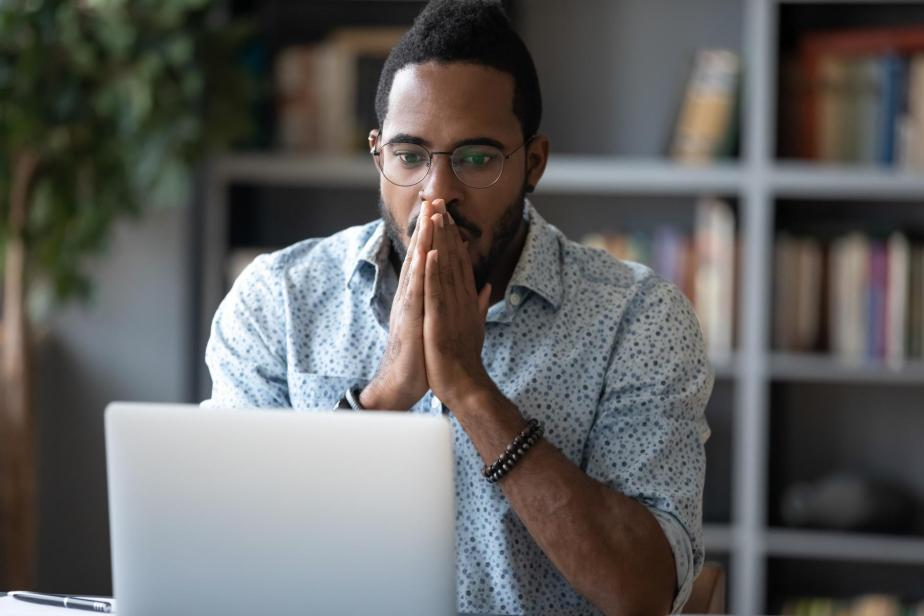 Shocked african business man feel frustrated looking at laptop screen