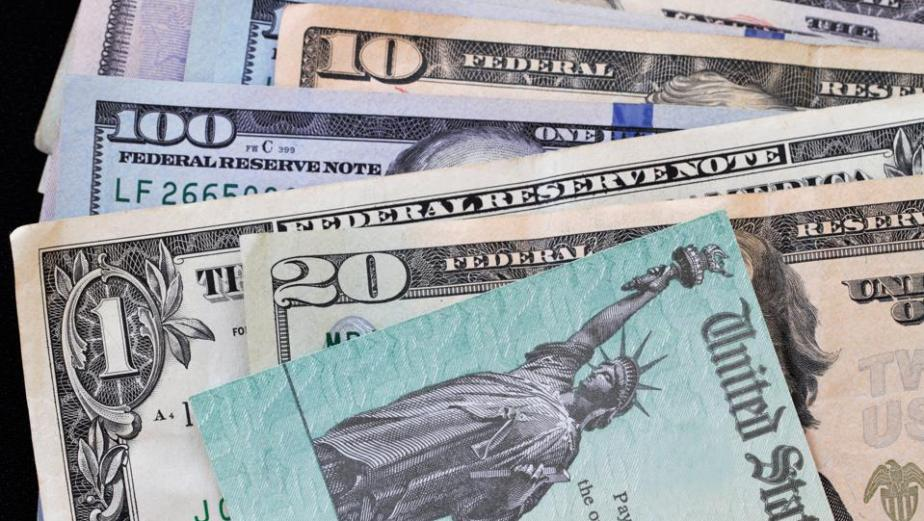 Treasury check on top of various currency bills - corona virus relief