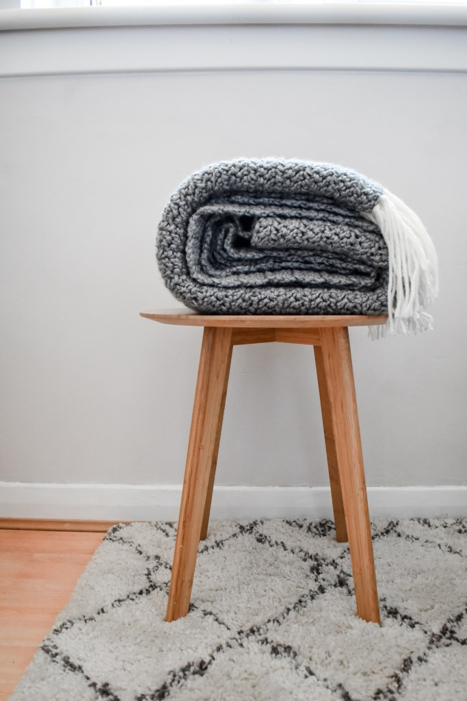 Folded grey blanket with cream tassels on stool