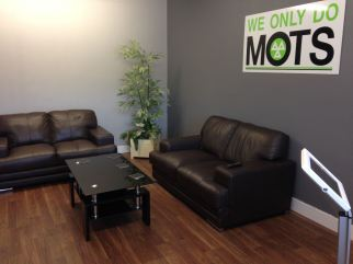 Gallery of images waiting room with sign we only do mots, leather sofas and coffee table with plant in the corner