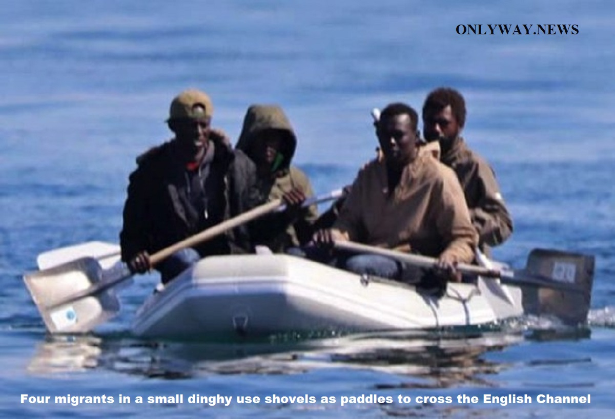 Four migrants in a small dinghy use shovels as paddles to cross the English Channel