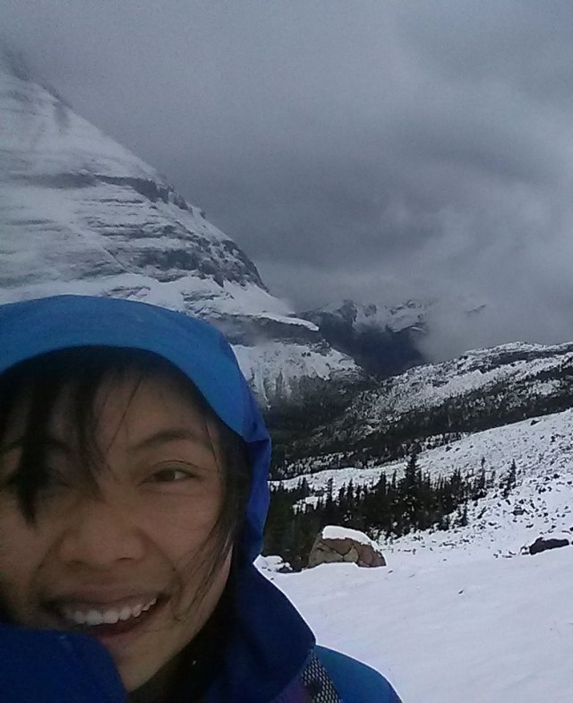 Girl in blue hood smiling at the camera, standing in front of snowy mountains.
