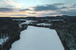 Forêt sous la neige lors du coucher de soleil au Québec en hiver