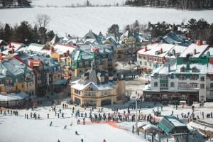 Station du Mont Tremblant et skieurs au Québec vu des pistes