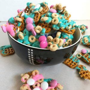 Pretzels mixed with colorful chocolate pieces, cereal pieces and melted colorful chocolate in a bowl
