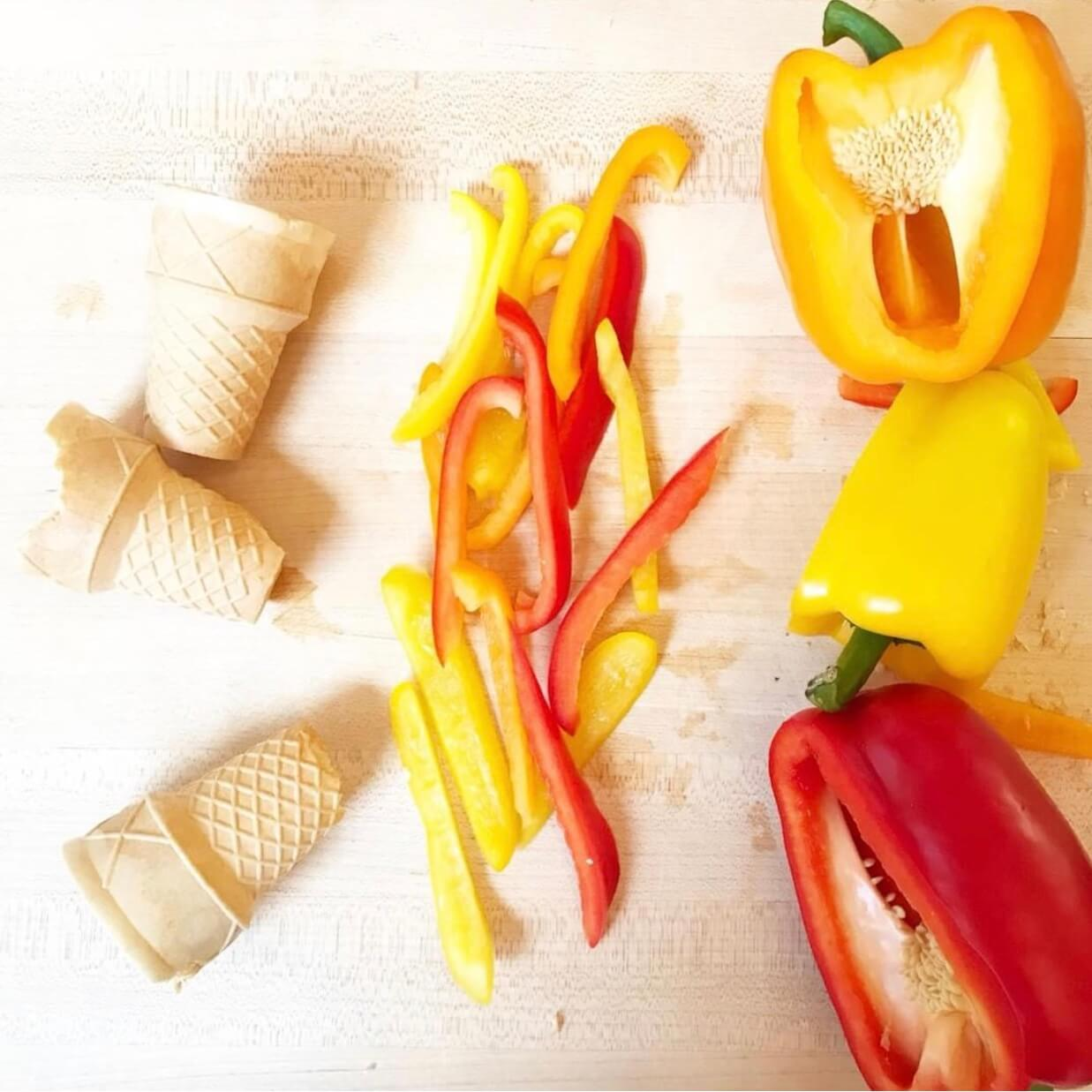 Three ice cream cones, colorful yellow, red and orange bell peppers both sliced and hole prepping to become an olympics torch snack.