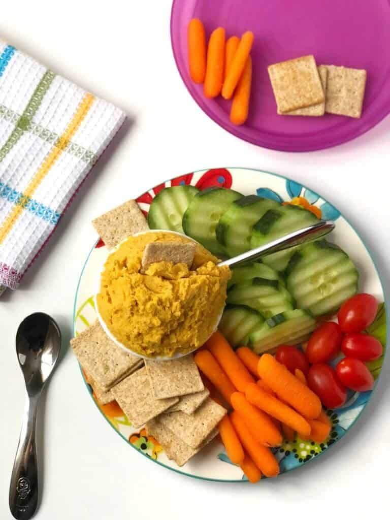 Close up of a platter of vegetable dip next to vegetables and crackers