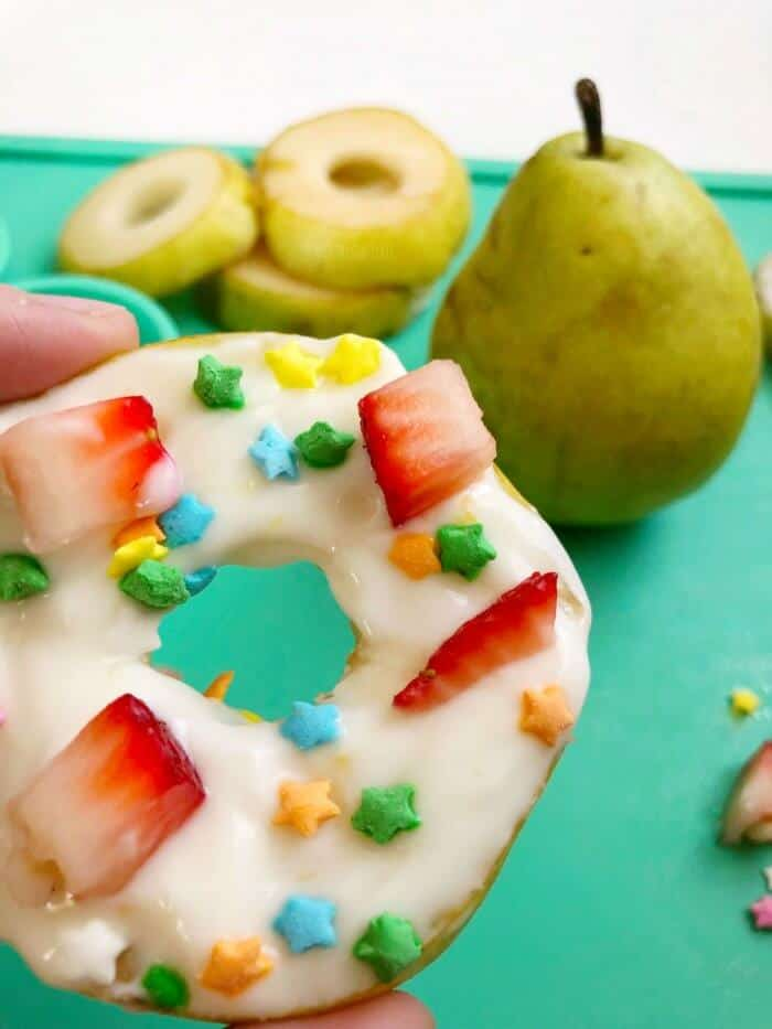 Close up of a pear slice decorated with yogurt, sprinkles and fruit pieces to look like a donut with more pear in the background