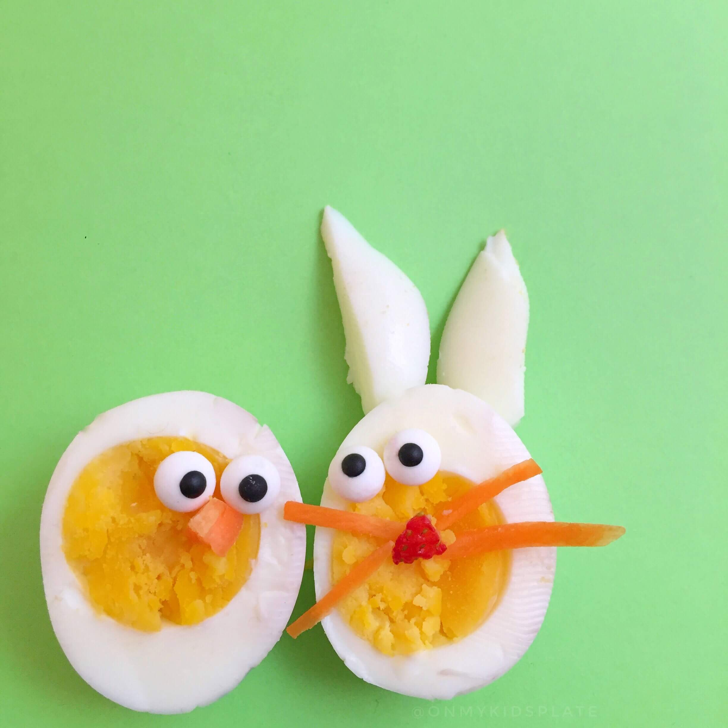 Hard-boiled eggs on a green background cut in half decorated like a rabbit and a chick.